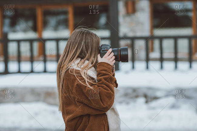 Blonde woman taking photos on snow road in winter