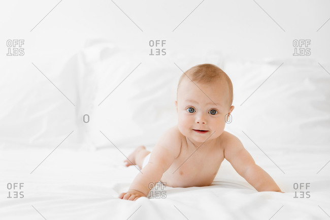 Funny baby lying on belly on white bed