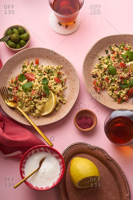 Traditional lebanese tabouli salad with fresh mint, parsley and tomatoes on pink background