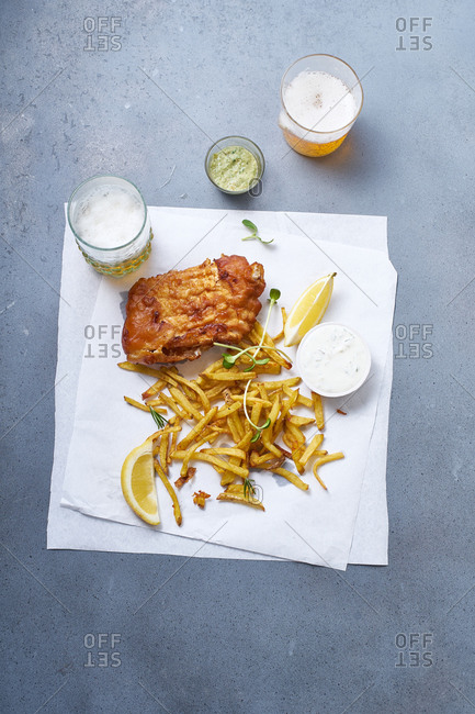 Fish and chips with beer , lemon slices and sauce