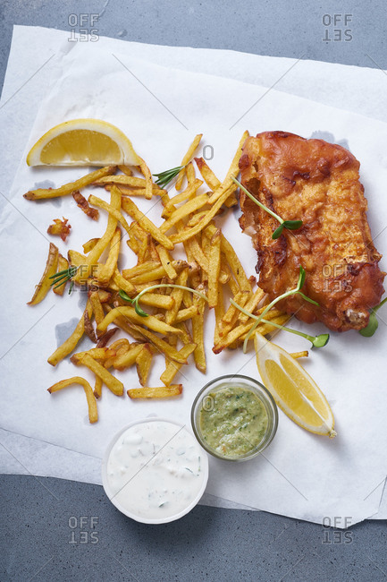 Fish and chips with beer, lemon slices and sauce
