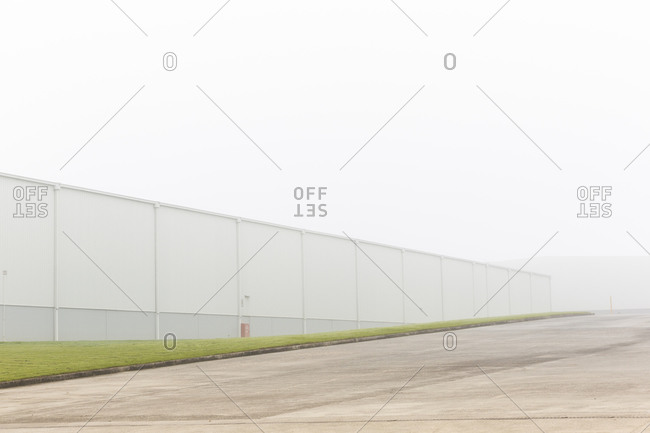 Minimalist background with concrete ground and green grass with metal fence in foggy day with grey sky
