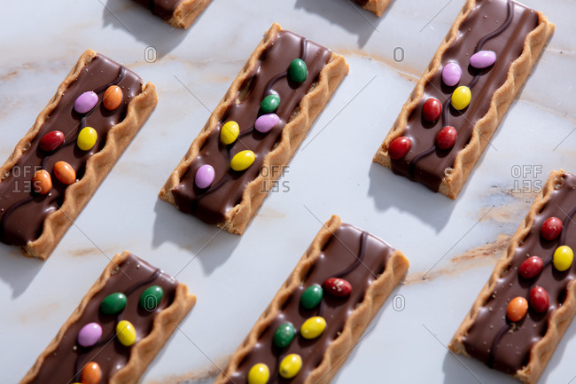 Cookies with dragee in chocolate and serpentine edges