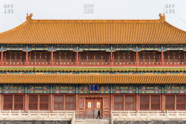 March 27, 2019: Man walking in front a pavilion in the Forbidden City. Beijing, China