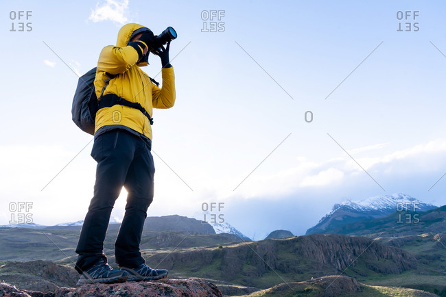 Alone hiker with yellow jacket taking pictures with a camera of the Andes. Patagonia, Argentina