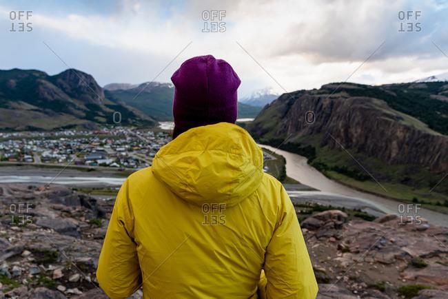 Alone hiker with yellow jacket admiring views over El Chalten village. Patagonia, Argentina