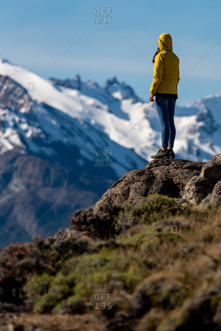 Hiker with yellow jacket admiring views over the Andes. Patagonia, Argentina