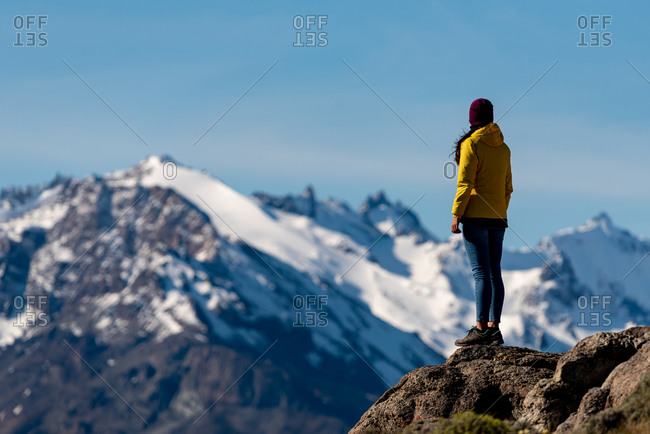 Alone hiker with yellow jacket admiring views over the Andes. Patagonia, Argentina
