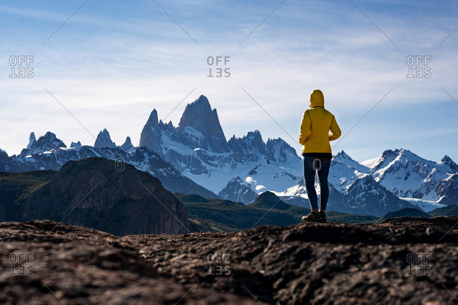 Alone hiker with yellow jacket admiring views over Mount Fitz Roy on the Andes. Patagonia, Argentina