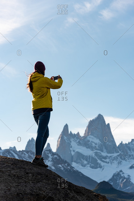 Alone hiker with yellow jacket taking pictures over Mount Fitz Roy on the Andes. Patagonia, Argentina