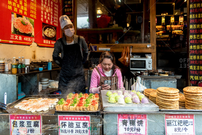 March, 15. 2019: Couple selling food on street of Lijiang's old town (Dayan). Yunnan, China