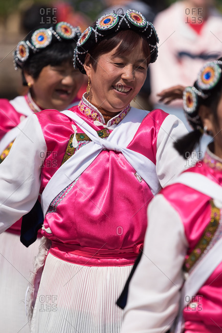 March 16, 2019: Laughing woman dancing in traditional costume of the Naxi ethnic group. Lijiang, China