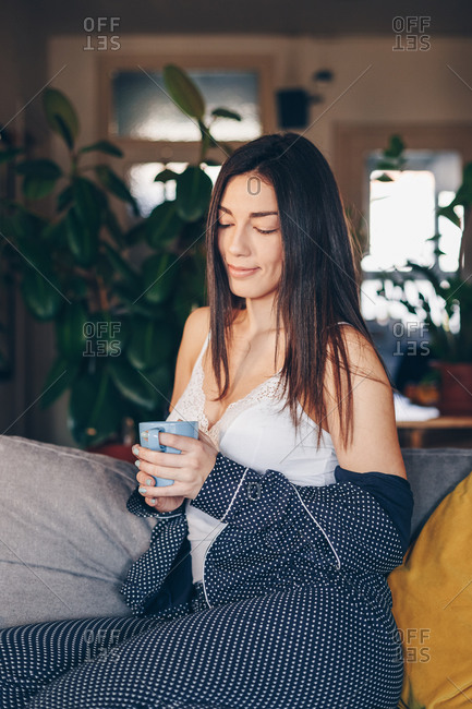 Portrait of beautiful happy young woman drinking morning coffee at her home