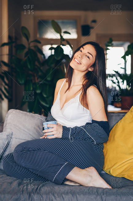 Portrait of beautiful happy young woman drinking morning coffee at her home. Posing for the camera and smiling