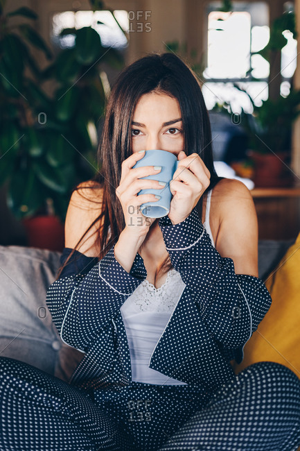 Portrait of attractive brunette young woman drinking morning coffee at her home