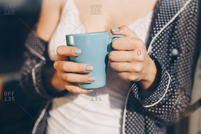 Detail of woman wearing pyjama and holding a coffe mug in hand. Morning coffee at home. Shot through the window, with city reflections