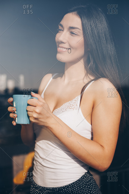 Portrait of beautiful happy young woman drinking morning coffee at her home. Shot through the window, with city reflections