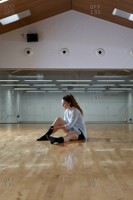 Side view of woman straightening her socks in a dance studio