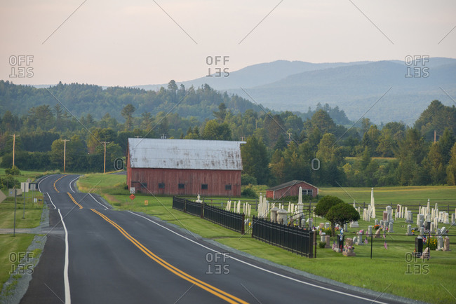 Scenic landscape with barn, cemetery and mountains in East Burke, Vermont