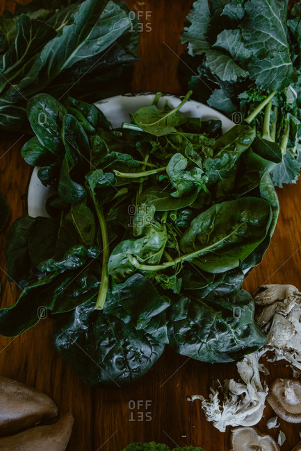 Spinach leaves in a bowl on wooden table