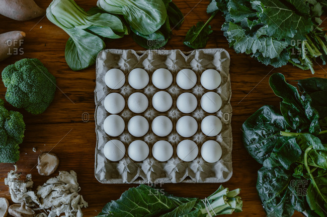 Overhead view of veggies surrounding carton filled with white eggs