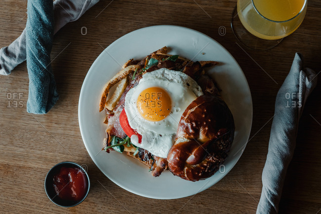 Overhead view of a breakfast sandwich with egg and a mimosa