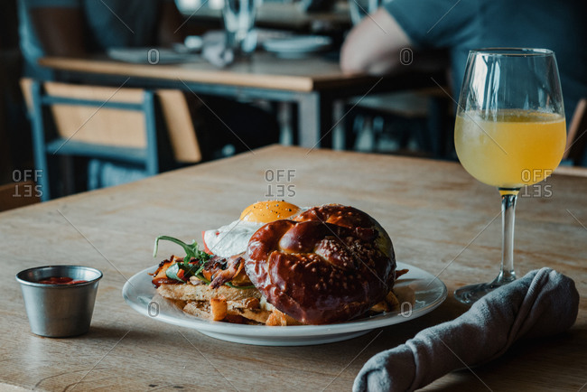 Breakfast sandwich with egg and a mimosa in a restaurant