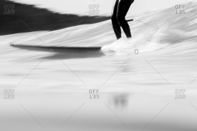 Blurred motion shot of surfer riding a wave in black and white