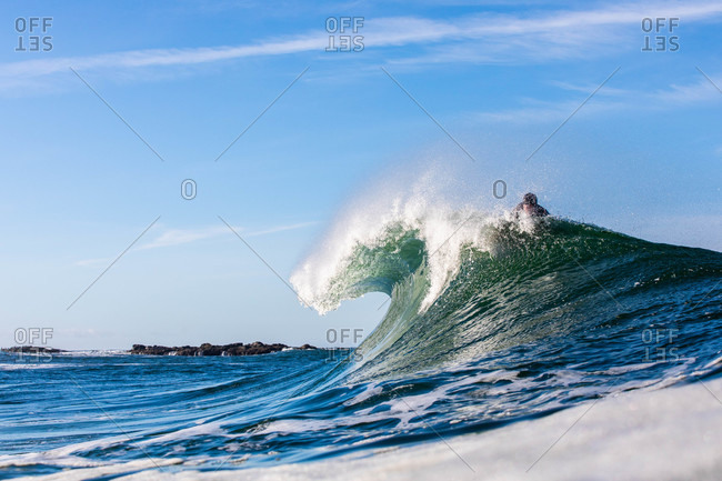 Surfer on a large wave cresting in the ocean