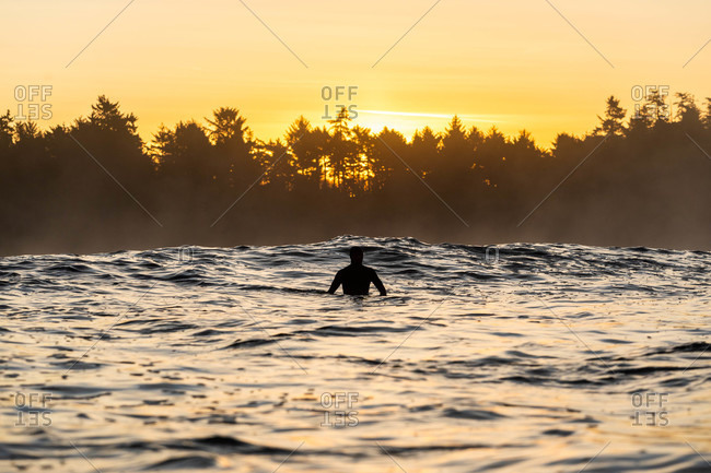 Surfer in the ocean at sunset