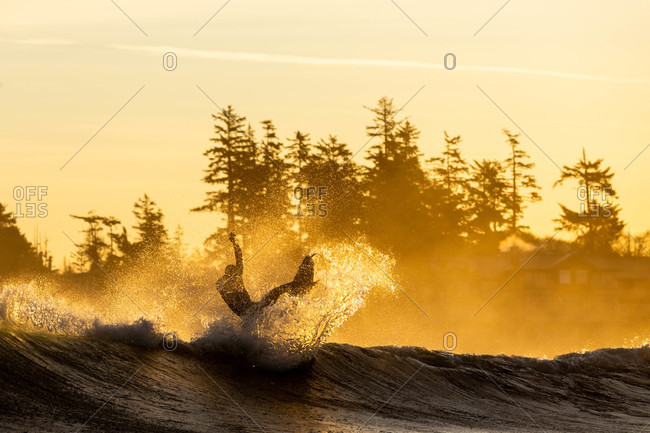 Surfer riding a wave at sunrise