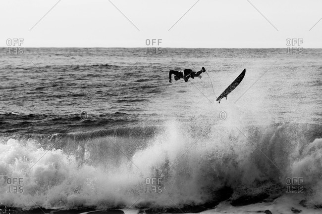 Motion shot of surfer catching big air while riding a wave in black and white