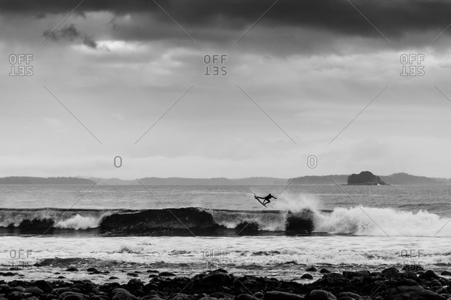 Monochromatic shot of surfer catching big air while surfing