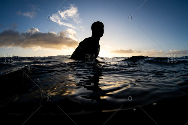 Silhouette of surfer sitting in the water