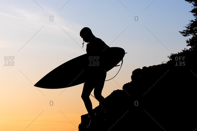 Silhouette of surfer carrying board down a hill