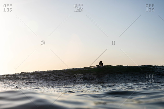 Silhouette of surfer preparing to ride wave