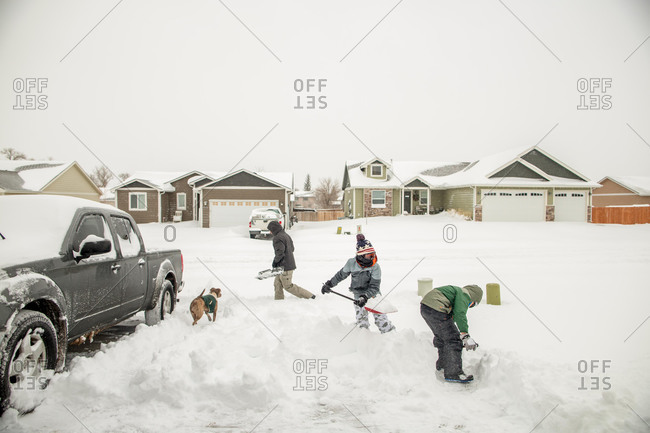Father and sons shoveling snow in driveway