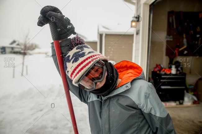Boy wearing ski goggles while shoveling snow