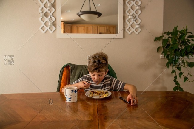 Young boy sitting at dining room table eating eggs