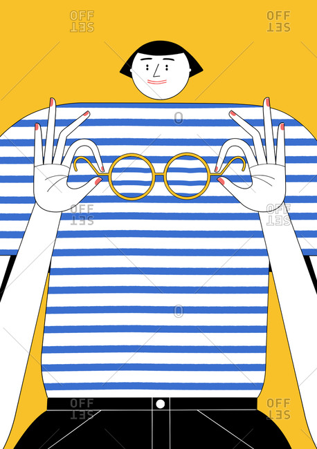 Woman holding eyeglasses in front of her striped shirt