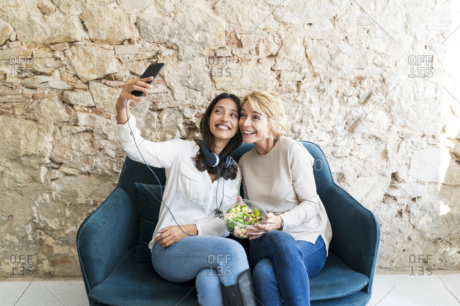 Two colleagues sitting on couch at lunchtime taking selfie with smartphone
