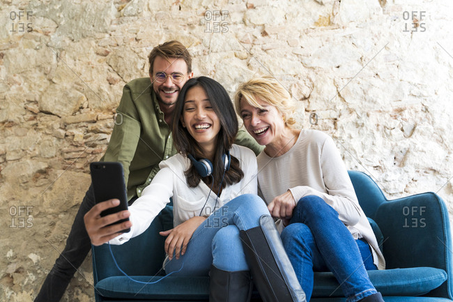 Three laughing colleagues in a studio taking selfie with smartphone