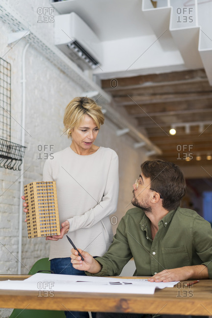 Two architects with architectural model in an office