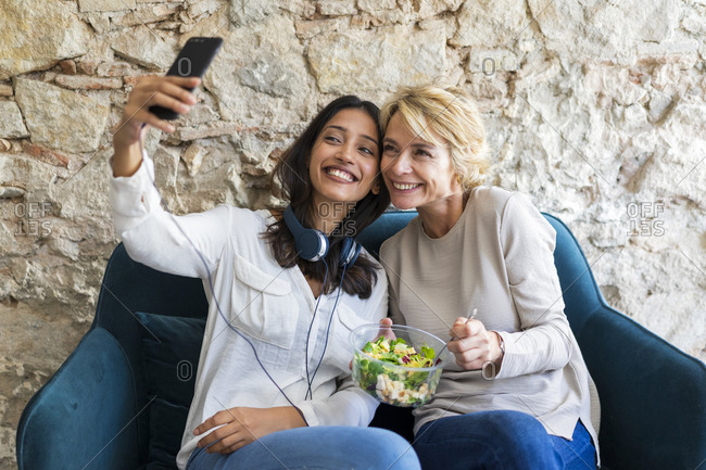 Two happy colleagues sitting on couch at lunchtime taking selfie with smartphone