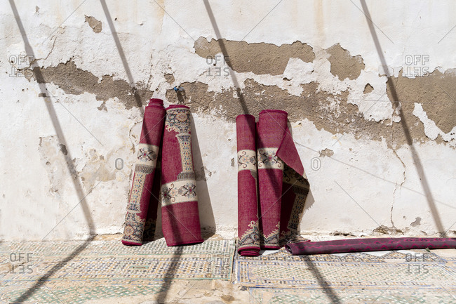 Four rolled up carpets leaning against wall at sunlight- Fez- Morocco