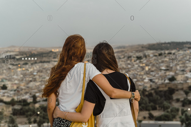 Back view of two best friends enjoying city view arm in arm in the evening- Fez- Morocco