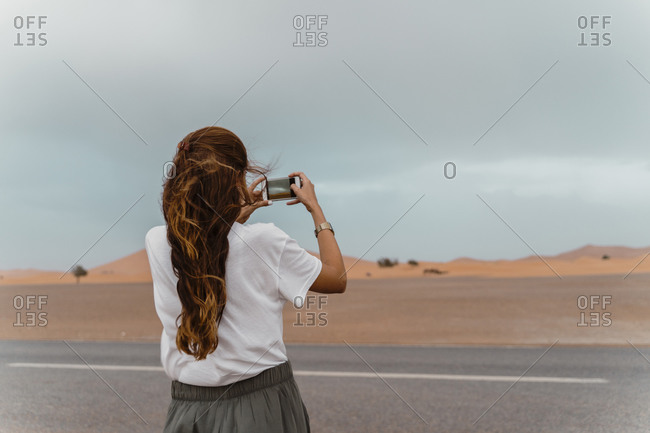 Back view of young woman standing  roadside taking photo with smartphone- Fez- Morocco
