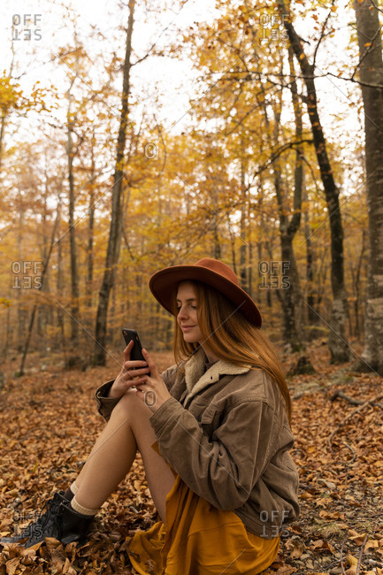 Fashionable redheaded young woman sitting in autumnal forest looking at cell phone