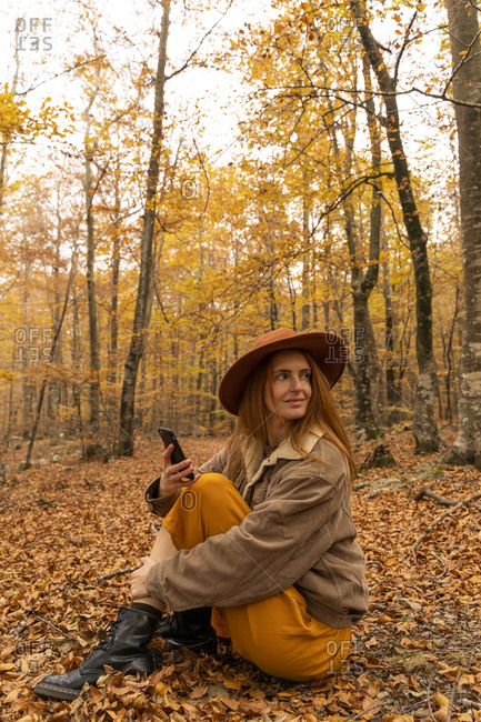 Portrait of fashionable redheaded young woman with cell phone sitting in autumnal forest around