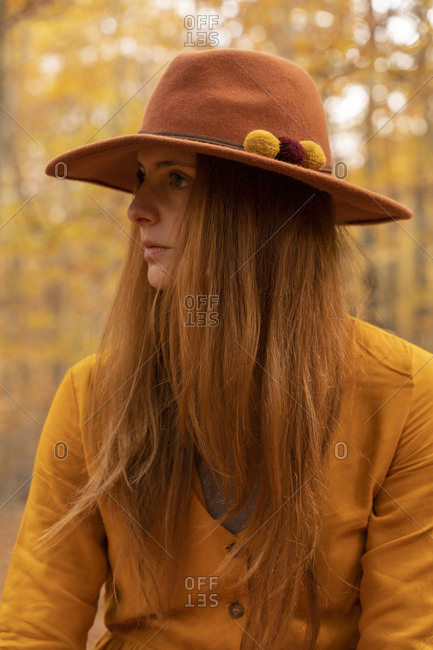 Portrait of fashionable redheaded young woman wearing felt hat in autumnal forest